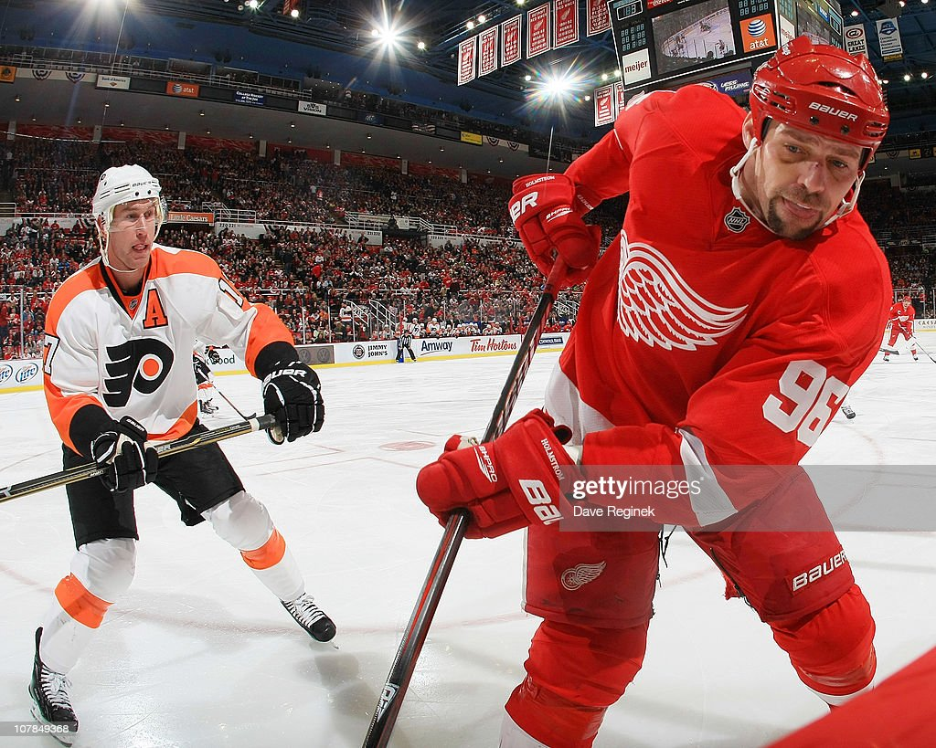 Tomas Holmstrom #96 of the Detroit Red Wings moves the puck from the boards followed by Jeff Carter #17 of the Philadelphia Flyers during an NHL game at Joe Louis Arena on January 2, 2011 in Detroit, Michigan. Flyers beat Wings 3-2