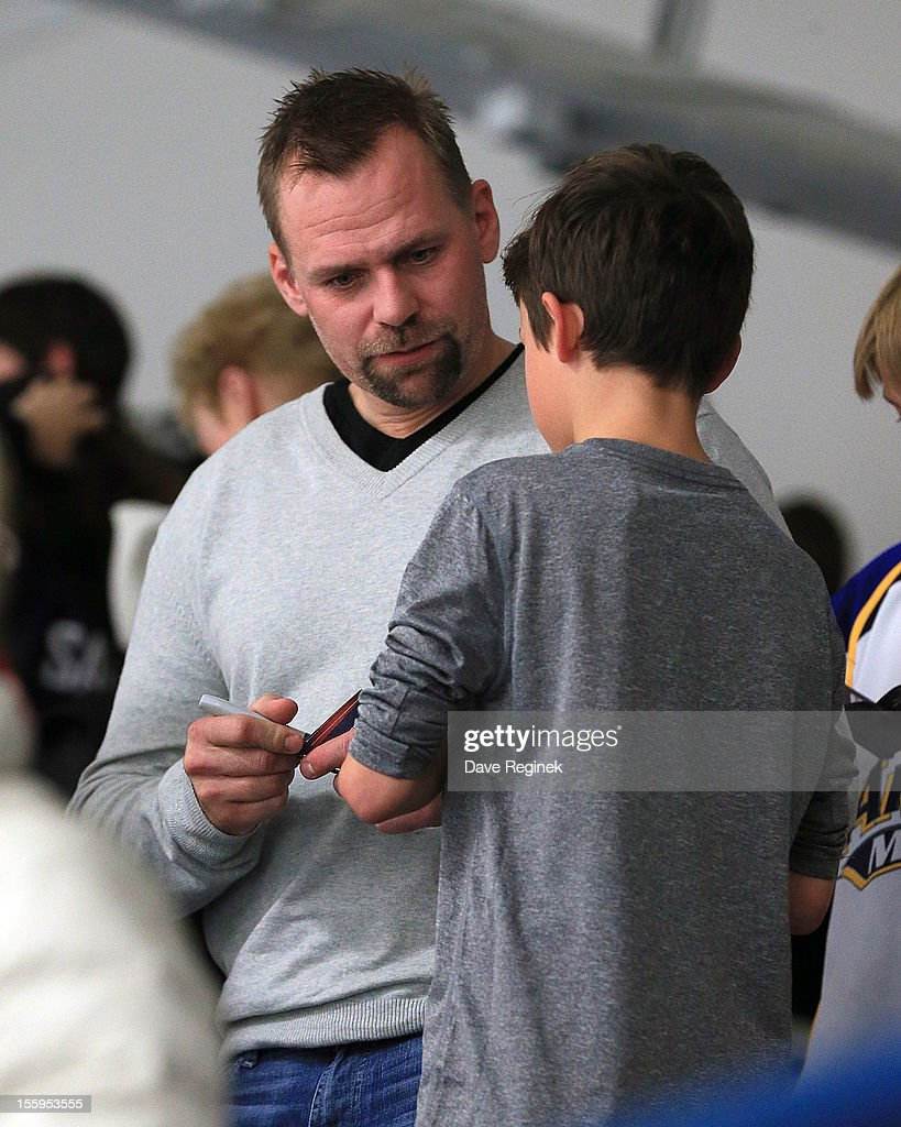 Tomas Holmstrom #96 of the Detroit Red Wings signs an autograph for a young fan attending the game between Sweden and the USA during the U-18 Four Nations Cup tournament on November 9, 2012 at the Ann Arbor Ice Cube in Ann Arbor, Michigan. USA won 5-3.