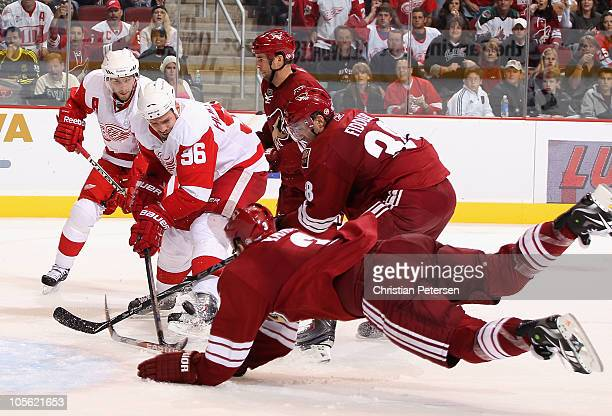 Tomas Holmstrom of the Detroit Red Wings skates in with the puck past Vernon Fiddler and Keith Yandle of the Phoenix Coyotes during the NHL game at...