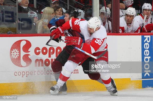 Tomas Holstrom of the Detroit Red Wings checks Kevin Porter of the Colorado Avalanche at the Pepsi Center on January 10 2011 in Denver Colorado