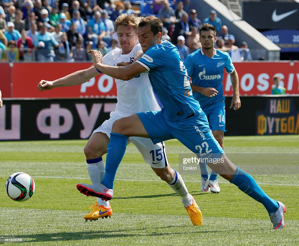 Tomas Hubocan (L) of FC Dinamo Moscow and Artem Dzyuba (C) of FC Zenit St. Petersburg vie for the ball during the Russian Football League match between FC Zenit St. Petersburg and FC Dinamo Moscow at the Petrovsky stadium on July 19, 2015 in St. Petersburg, Russia.