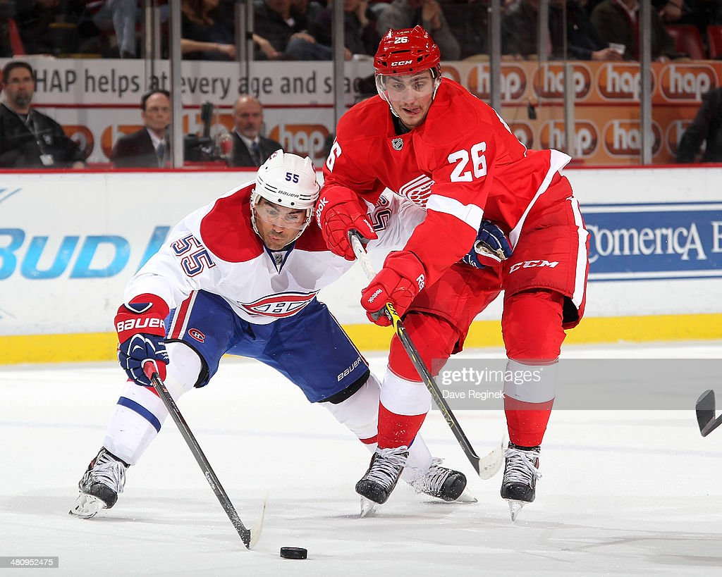 Tomas Jurco #26 of the Detroit Red Wings and <a gi-track='captionPersonalityLinkClicked' href=/galleries/search?phrase=Francis+Bouillon&family=editorial&specificpeople=215165 ng-click='$event.stopPropagation()'>Francis Bouillon</a> #55 of the Montreal Canadiens battle for the puck during an NHL game on March 27, 2014 at Joe Louis Arena in Detroit, Michigan.
