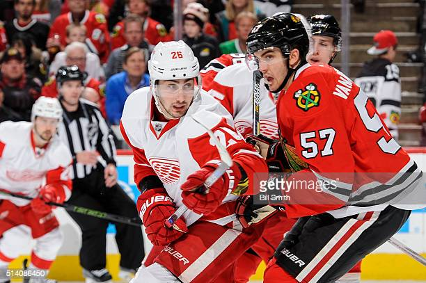 Tomas Jurco of the Detroit Red Wings and Trevor van Riemsdyk of the Chicago Blackhawks watch for the puck in the third period of the NHL game at the...