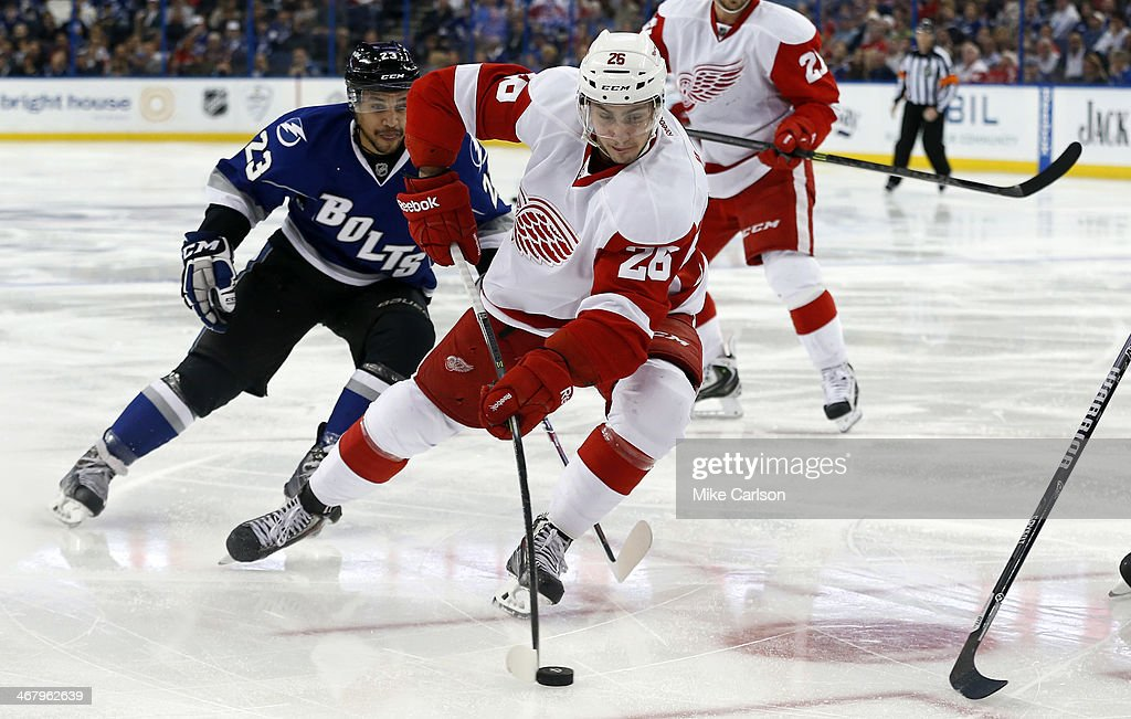 Tomas Jurco #26 of the Detroit Red Wings avoids the check of J.T. Brown #23 of the Tampa Bay Lightning at the Tampa Bay Times Forum on February 8, 2014 in Tampa, Florida.
