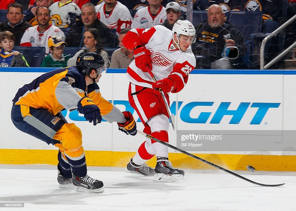 Tomas Jurco #26 of the Detroit Red Wings fires the puck while defended by <a gi-track='captionPersonalityLinkClicked' href=/galleries/search?phrase=Jamie+McBain&family=editorial&specificpeople=543199 ng-click='$event.stopPropagation()'>Jamie McBain</a> #4 of the Buffalo Sabres on April 8, 2014 at the First Niagara Center in Buffalo, New York.
