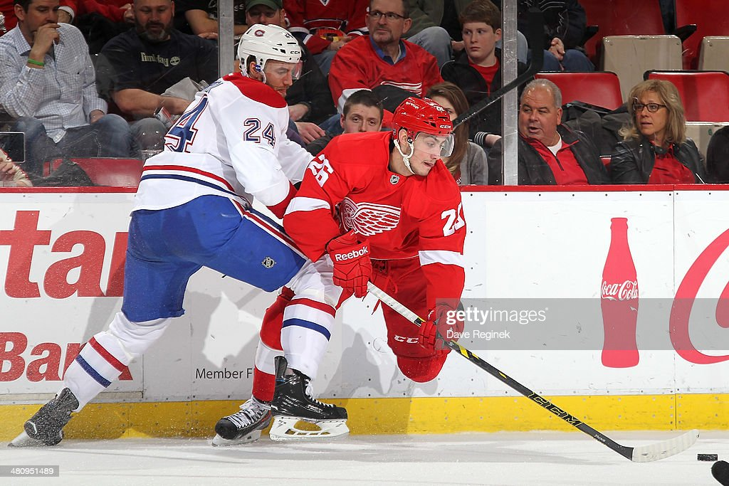 Tomas Jurco #26 of the Detroit Red Wings makes a move with the puck as <a gi-track='captionPersonalityLinkClicked' href=/galleries/search?phrase=Jarred+Tinordi&family=editorial&specificpeople=7029368 ng-click='$event.stopPropagation()'>Jarred Tinordi</a> #24 of the Montreal Canadiens defends him during an NHL game on March 27, 2014 at Joe Louis Arena in Detroit, Michigan.