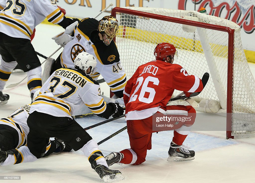 Tomas Jurco #26 of the Detroit Red Wings scores a third period goal as Tuukka Rask #40 and Patrice Bergenron #37 of the Boston Bruins defend during the game at Joe Louis Arena on April 2, 2014 in Detroit, Michigan. The Red Wings defeated the Bruins 3-2