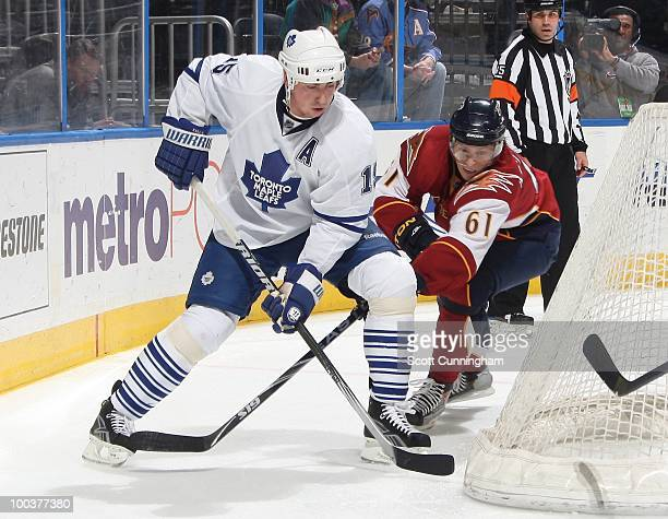 Tomas Kaberle of the Toronto Maple Leafs defends against Maxim Afinogenov of the Atlanta Thrashers at Philips Arena on March 25 2010 in Atlanta...