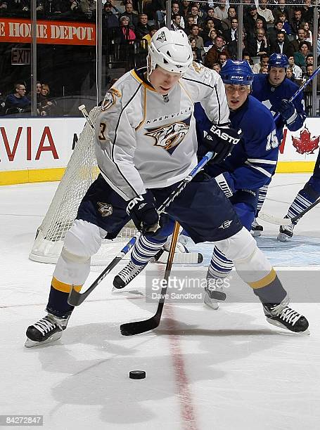 Tomas Kaberle of the Toronto Maple Leafs defends against Wade Belak of the Nahville Predators during their NHL game at the Air Canada Centre January...