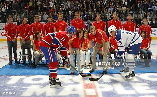 Tomas Kaberle of the Toronto Maple Leafs takes part in ceremonial faceoff with Saku Koivu of the Montreal Canadiens and all 20 Canadian Olympic...