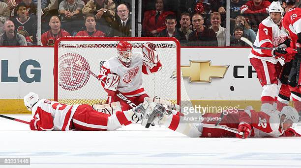 Tomas Kopecky and Kris Draper of the Detroit Red Wings drop to the ice to block a shot for Chris Osgood of the Detroit Red Wings against the Ottawa...