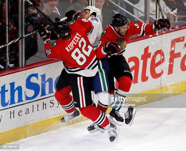 Tomas Kopecky and Kris Versteeg of the Chicago Blackhawks combine to check Kevin Bieksa of the Vancouver Canucks in Game One of the Western...