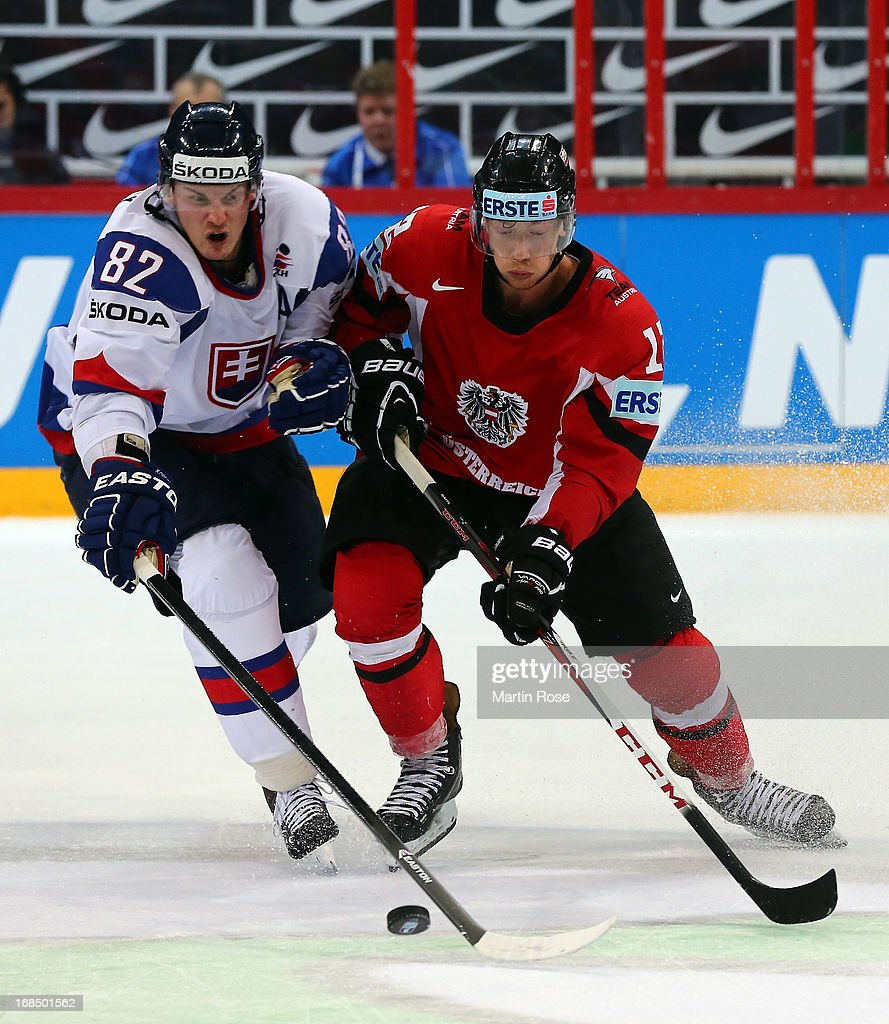 Tomas Kopecky (L) of Slovakia and Michael Raffl (R) of Austria battle for the puck during the IIHF World Championship group H match between Slovakia and Austria at Hartwall Areena on May 10, 2013 in Helsinki, Finland.