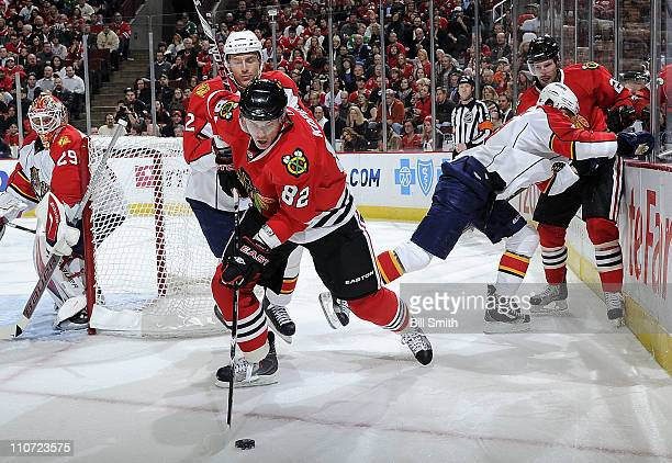 Tomas Kopecky of the Chicago Blackhawks and Alexander Sulzer of the Florida Panthers skate after the puck as Panthers' goalie Tomas Vokoun watches...