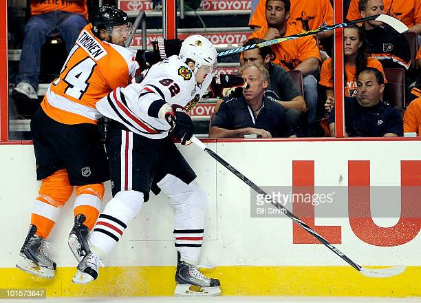 Tomas Kopecky of the Chicago Blackhawks and Kimmo Timonen of the Philadelphia Flyers crash into the boards during the first period of Game Three of...