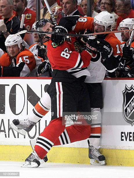 Tomas Kopecky of the Chicago Blackhawks checks Mike Richards of the Philadelphia Flyers into the Flyers bench in the first period of Game Two of the...