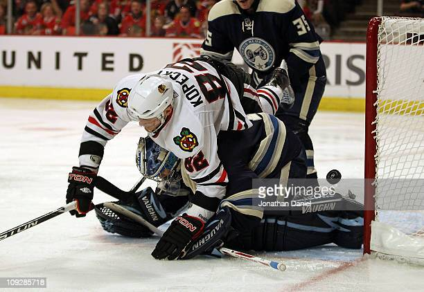 Tomas Kopecky of the Chicago Blackhawks falls over Steve Mason of the Columbus Blue Jackets and is called for goaltender interference at the United...