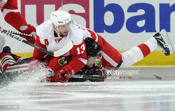 Tomas Kopecky of the Chicago Blackhawks gets squished by Pavel Datsyuk of the Detroit Red Wings on April 10 2011 at the United Center in Chicago...