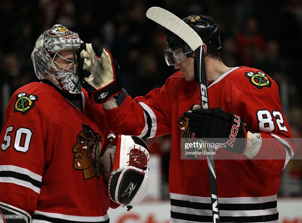 Tomas Kopecky of the Chicago Blackhawks playfully smacks teammate Corey Crawford in the face after a win over the Detroit Red Wings at the United...