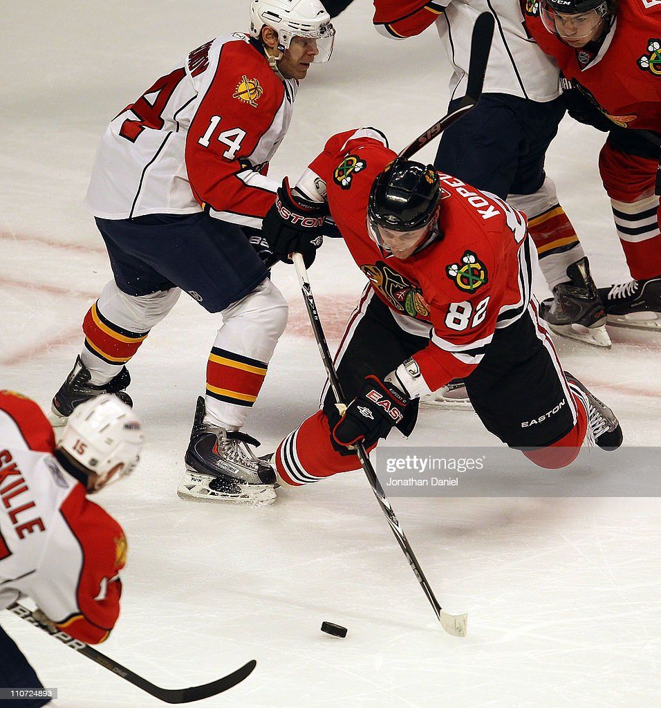 <a gi-track='captionPersonalityLinkClicked' href=/galleries/search?phrase=Tomas+Kopecky&family=editorial&specificpeople=2234349 ng-click='$event.stopPropagation()'>Tomas Kopecky</a> #82 of the Chicago Blackhawks shoots the puck between <a gi-track='captionPersonalityLinkClicked' href=/galleries/search?phrase=Sergei+Samsonov&family=editorial&specificpeople=202831 ng-click='$event.stopPropagation()'>Sergei Samsonov</a> #14 and <a gi-track='captionPersonalityLinkClicked' href=/galleries/search?phrase=Jack+Skille&family=editorial&specificpeople=697014 ng-click='$event.stopPropagation()'>Jack Skille</a> #15 of the Florida Panthers at the United Center on March 23, 2011 in Chicago, Illinois.