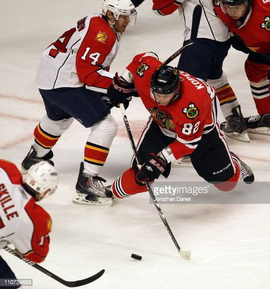Tomas Kopecky of the Chicago Blackhawks shoots the puck between Sergei Samsonov and Jack Skille of the Florida Panthers at the United Center on March...