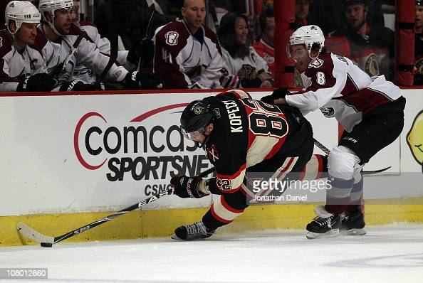 Tomas Kopecky of the Chicago Blackhawks tries to control the puck under pressure from Kevin Shattenkirk of the Colorado Avalanche at the United...