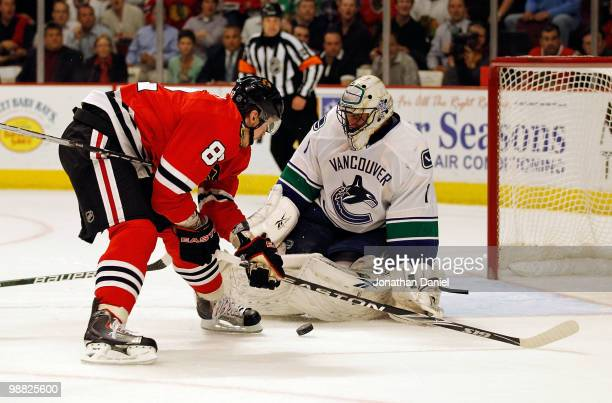 Tomas Kopecky of the Chicago Blackhawks tries to get off a shot against Roberto Luongo of the Vancouver Canucks in Game Two of the Western Conference...