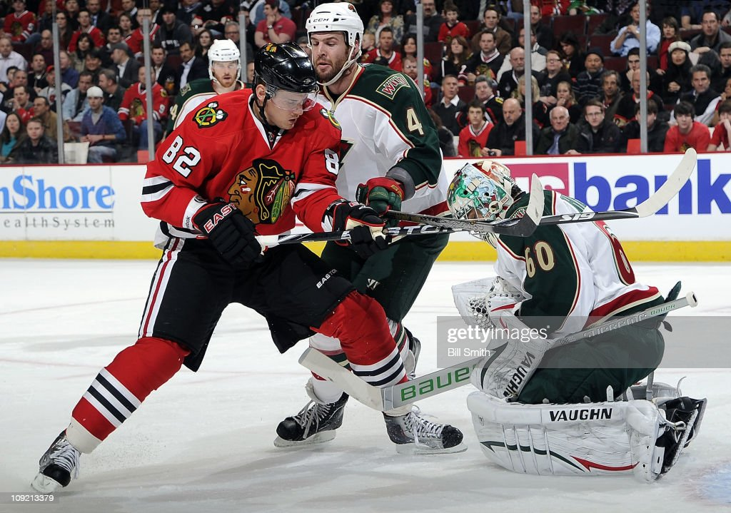 <a gi-track='captionPersonalityLinkClicked' href=/galleries/search?phrase=Tomas+Kopecky&family=editorial&specificpeople=2234349 ng-click='$event.stopPropagation()'>Tomas Kopecky</a> #82 of the Chicago Blackhawks watches as goalie Jose Theodore #60 of the Minnesota Wild stops the puck and <a gi-track='captionPersonalityLinkClicked' href=/galleries/search?phrase=Clayton+Stoner&family=editorial&specificpeople=2222214 ng-click='$event.stopPropagation()'>Clayton Stoner</a> #4 of the Wild skates in from the side on February 16, 2011 at the United Center in Chicago, Illinois.