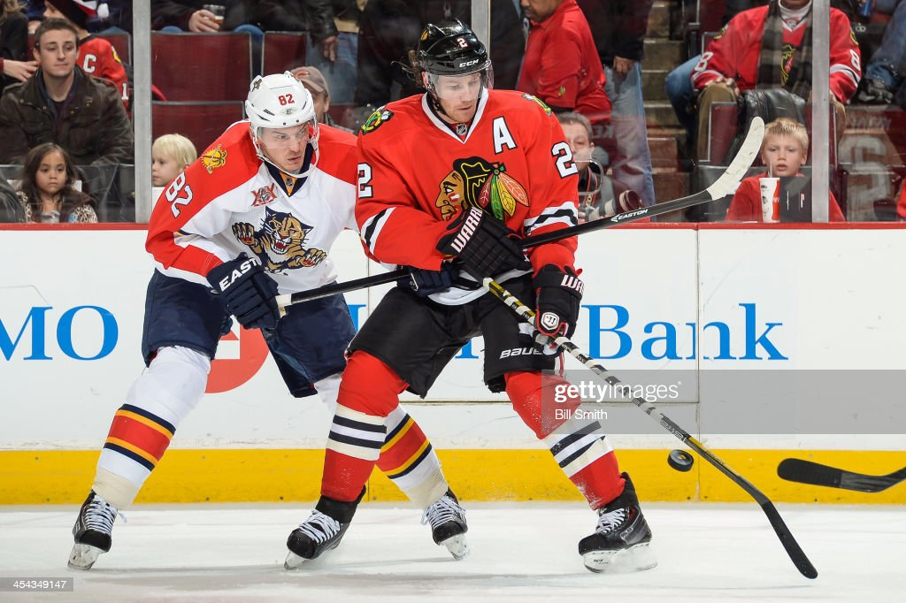 Tomas Kopecky #82 of the Florida Panthers and Duncan Keith #2 of the Chicago Blackhawks battle for the puck during the NHL game on December 08, 2013 at the United Center in Chicago, Illinois.