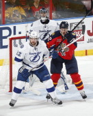 Tomas Kopecky of the Florida Panthers battles with JeanPhilippe Cote in front of goaltender Ben Bishop of the Tampa Bay Lightning at the BBT Center...