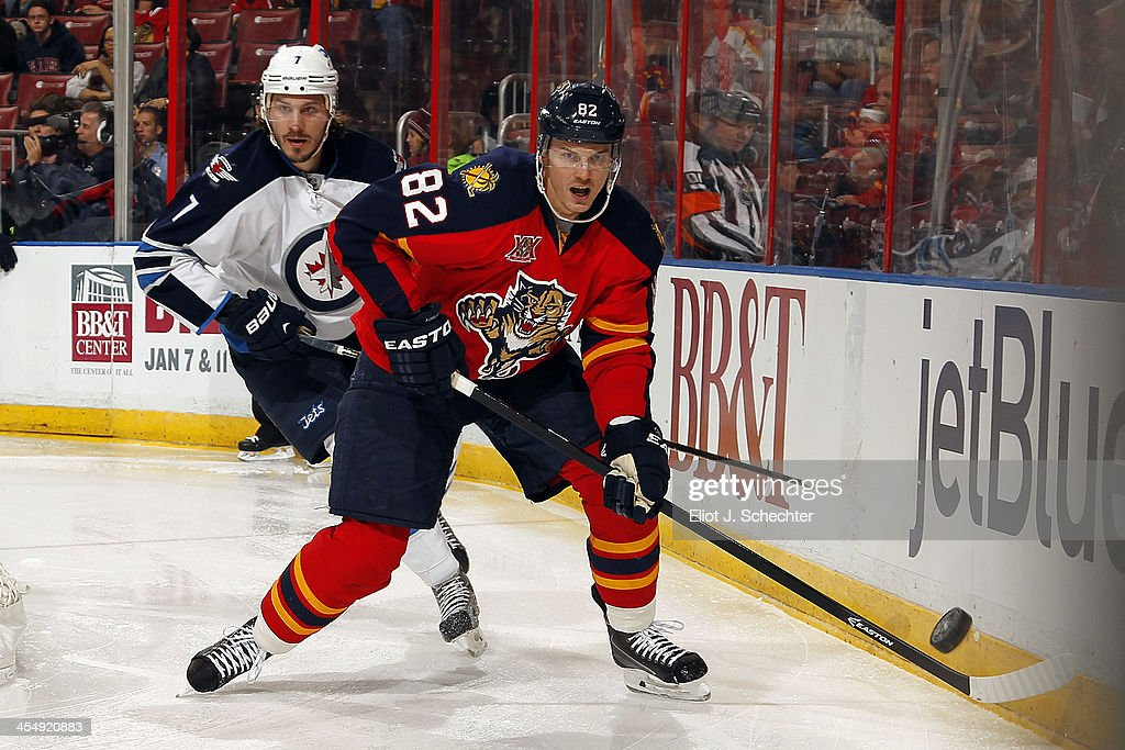 Tomas Kopecky #82 of the Florida Panthers digs the puck out from the boards against Keaton Ellerby #7 of the Winnipeg Jets at the BB&T Center on December 5, 2013 in Sunrise, Florida.