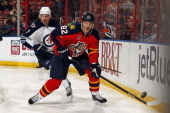 Tomas Kopecky of the Florida Panthers digs the puck out from the boards against Keaton Ellerby of the Winnipeg Jets at the BBT Center on December 5...