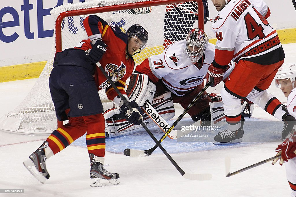 <a gi-track='captionPersonalityLinkClicked' href=/galleries/search?phrase=Tomas+Kopecky&family=editorial&specificpeople=2234349 ng-click='$event.stopPropagation()'>Tomas Kopecky</a> #82 of the Florida Panthers gets into position to tip in a shot in front of goaltender <a gi-track='captionPersonalityLinkClicked' href=/galleries/search?phrase=Dan+Ellis&family=editorial&specificpeople=2235265 ng-click='$event.stopPropagation()'>Dan Ellis</a> #31 of the Carolina Hurricanes during the seasons opener at the BB&T Center on January 19, 2013 in Sunrise, Florida.The Panthers defeated the Hurricanes 5-1.
