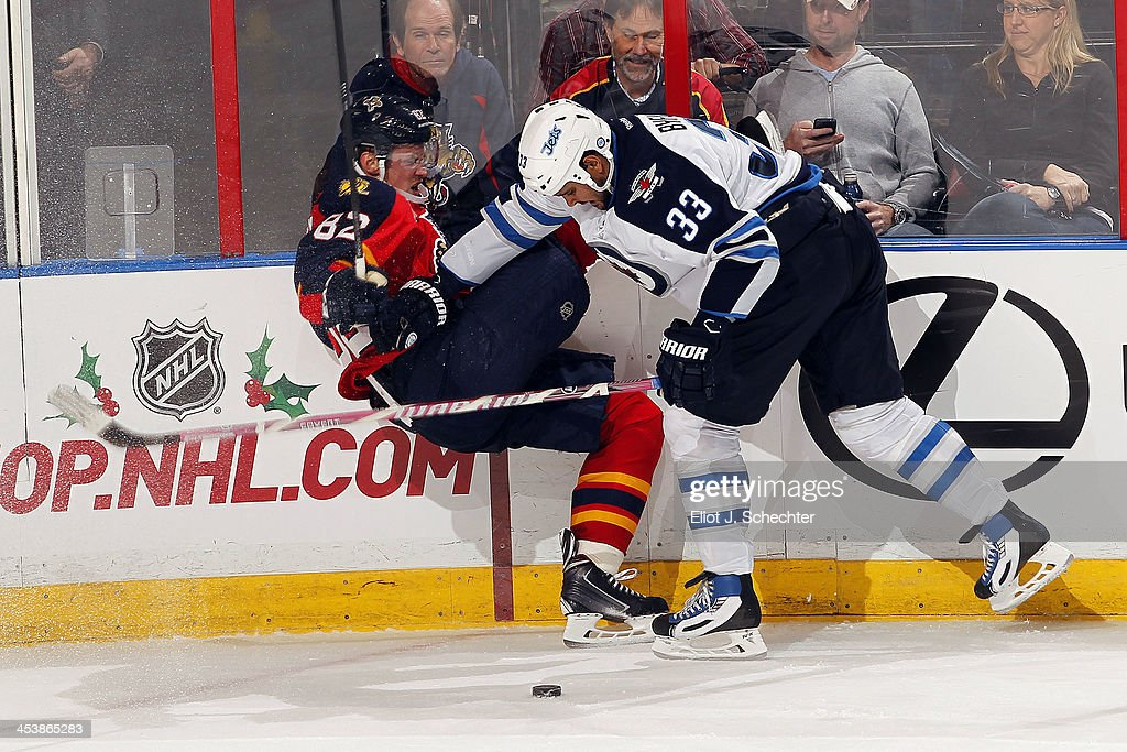 <a gi-track='captionPersonalityLinkClicked' href=/galleries/search?phrase=Tomas+Kopecky&family=editorial&specificpeople=2234349 ng-click='$event.stopPropagation()'>Tomas Kopecky</a> #82 of the Florida Panthers is checked by <a gi-track='captionPersonalityLinkClicked' href=/galleries/search?phrase=Dustin+Byfuglien&family=editorial&specificpeople=672505 ng-click='$event.stopPropagation()'>Dustin Byfuglien</a> #33 of the Winnipeg Jets at the BB&T Center on December 5, 2013 in Sunrise, Florida.