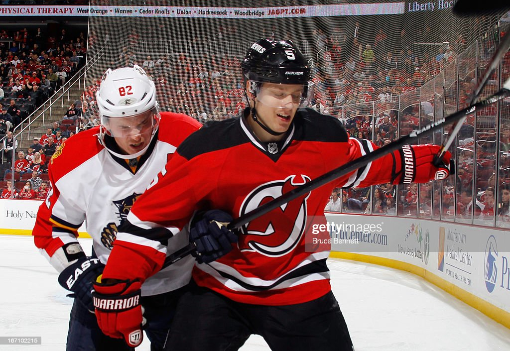 Tomas Kopecky #82 of the Florida Panthers rides Adam Larsson #5 of the New Jersey Devils into the boards at the Prudential Center on April 20, 2013 in Newark, New Jersey. The Devils defeated the Panthers 6-2.