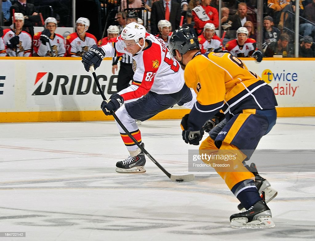 <a gi-track='captionPersonalityLinkClicked' href=/galleries/search?phrase=Tomas+Kopecky&family=editorial&specificpeople=2234349 ng-click='$event.stopPropagation()'>Tomas Kopecky</a> #82 of the Florida Panthers shoots the puck into the zone past <a gi-track='captionPersonalityLinkClicked' href=/galleries/search?phrase=Filip+Forsberg&family=editorial&specificpeople=8768623 ng-click='$event.stopPropagation()'>Filip Forsberg</a> #9 of the Nashville Predators at Bridgestone Arena on October 15, 2013 in Nashville, Tennessee.