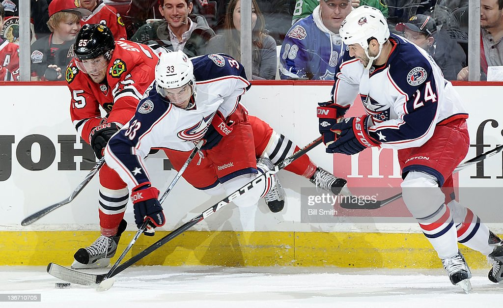 Tomas Kubalik #33 of the Columbus Blue Jackets goes airborne as teammate Derek Mackenzie #24 follows behind and Viktor Stalberg #25 of the Chicago Blackhawks reaches for the puck during the NHL game on January 10, 2012 at the United Center in Chicago, Illinois.