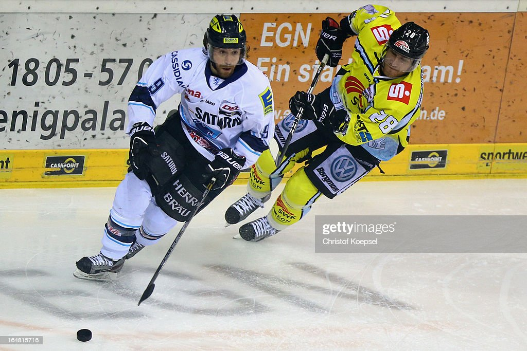 Tomas Kurka of Krefeld Pinguine (R) uses his stick against Jeff Likens of ERC Ingolstadt (L) during the fifth DEL Play-Off-match between Krefeld Pinguine and ERC Ingolstadt at Koenigspalast on March 28, 2013 in Wuppertal, Germany.