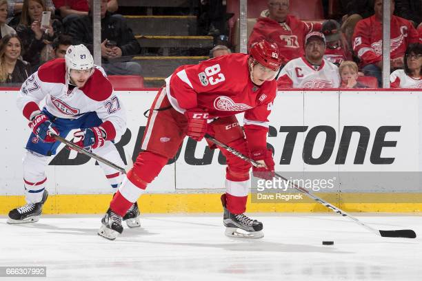 Tomas Nosek of the Detroit Red Wings skates with the puck followed by Alex Galchenyuk of the Montreal Canadiens during an NHL game at Joe Louis Arena...
