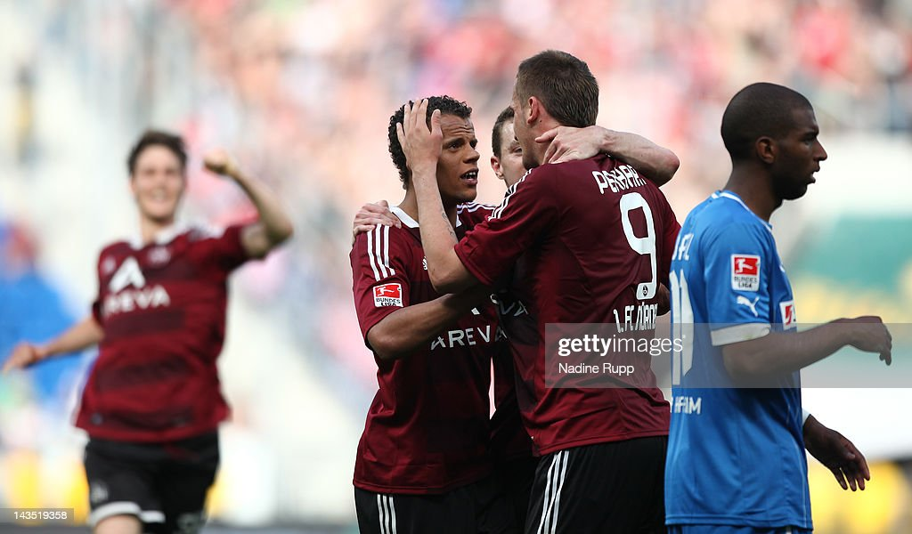 Tomas Pekhart of Nuernberg celebrates after scoring his team's third goal while Ryan Babel of Hoffenheim looks dejected during the Bundesliga match...