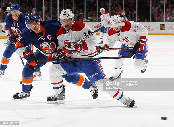 Tomas Plekanec of the Montreal Canadiens and Mark Streit of the New York Islanders battle for the puck at Nassau Veterans Memorial Coliseum on March...