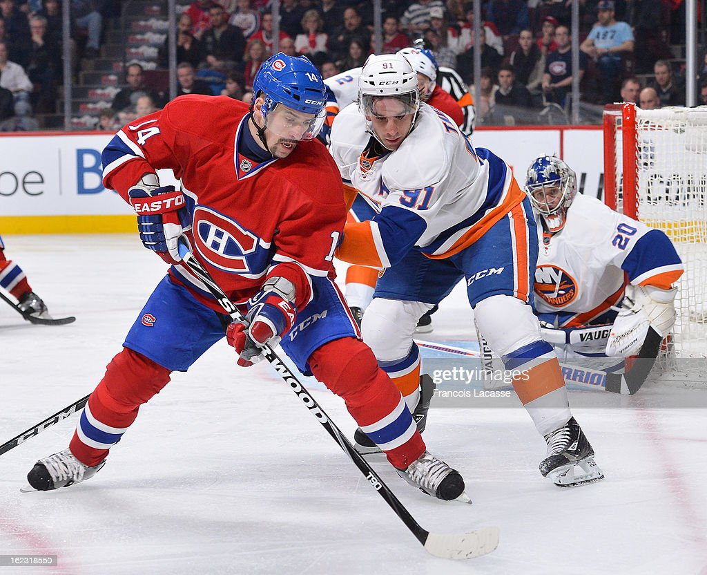 <a gi-track='captionPersonalityLinkClicked' href=/galleries/search?phrase=Tomas+Plekanec&family=editorial&specificpeople=620244 ng-click='$event.stopPropagation()'>Tomas Plekanec</a> #14 of the Montreal Canadiens battles for the puck with <a gi-track='captionPersonalityLinkClicked' href=/galleries/search?phrase=John+Tavares&family=editorial&specificpeople=601791 ng-click='$event.stopPropagation()'>John Tavares</a> #91 of the New York Islanders during the NHL game on February 21, 2013 at the Bell Centre in Montreal, Quebec, Canada.