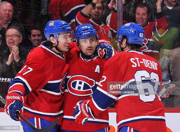 Tomas Plekanec of the Montreal Canadiens celebrates his first period goal with terammates Chris Campoli and Frederic StDenis during the NHL game...