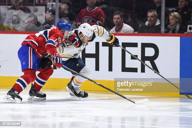 Tomas Plekanec of the Montreal Canadiens fights for the puck against Kyle Okposo of the Buffalo Sabres in the NHL game at the Bell Centre on November...