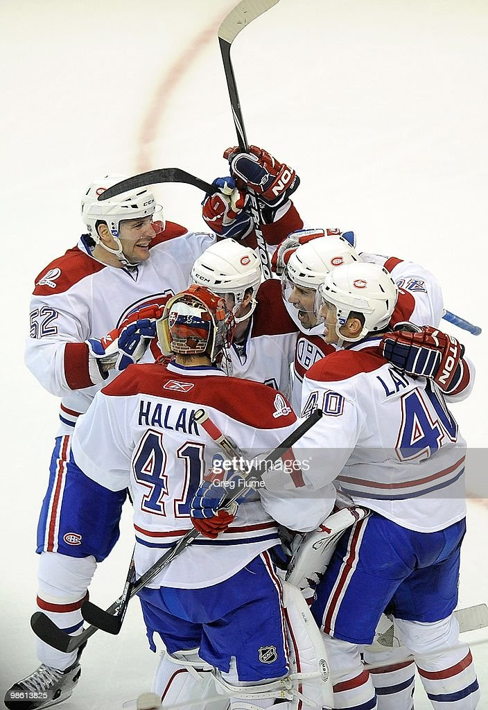 Tomas Plekanec of the Montreal Canadiens is mobbed by teammates after scoring the game winning goal in overtime against the Washington Capitals in...