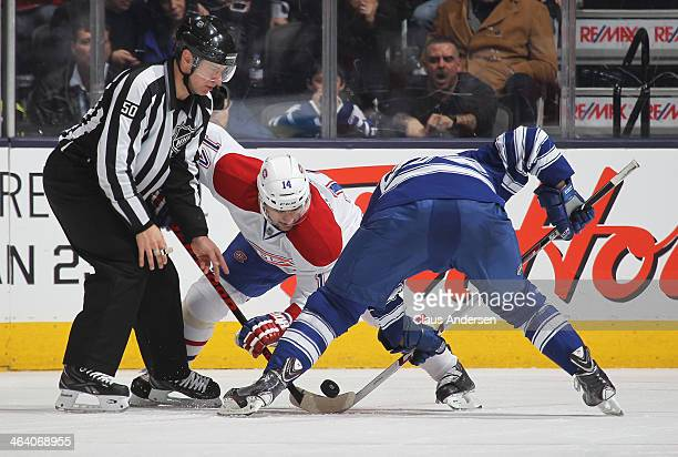 Tomas Plekanec of the Montreal Canadiens takes a faceoff against Peter Holland of the Toronto Maple Leafs during an NHL game at the Air Canada Centre...