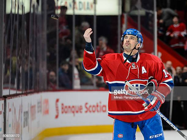 Tomas Plekanec of the Montreal Canadiens tosses a puck to fans after being named the first star during the NHL game against the Edmonton Oilers at...