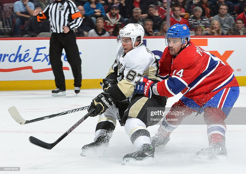 Tomas Plekanec #14 of the Montreal Canadiens tries to tie up Sidney Crosby #87 of the Pittsburgh Penguins as he looks for a loose puck during the NHL game on March 2, 2013 at the Bell Centre in Montreal, Quebec, Canada.