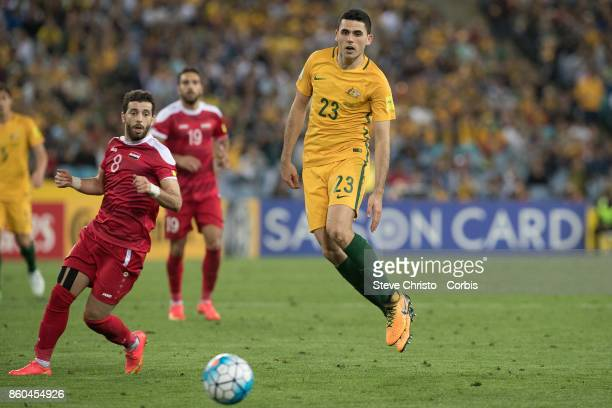 Tomas Rogic of Australia competes for the ball with Syria's Mahmoud Almawas during the 2018 FIFA World Cup Asian Playoff match between the Australian...