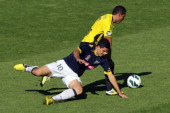 Tomas Rogic of the Mariners goes down while tackling Leo Bertos of the Phoenix during the round 12 ALeague match between the Wellington Phoenix and...